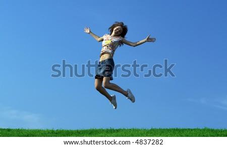 Girl jumping over green grass - stock photo