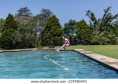 Girl Jumping Swim Pool Girl running jumping into swimming pool summer playtime. - stock photo