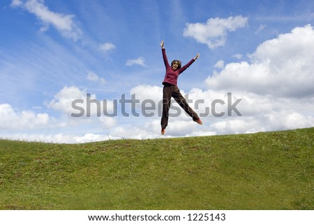 girl jumping with arms opened on grass and blue sky