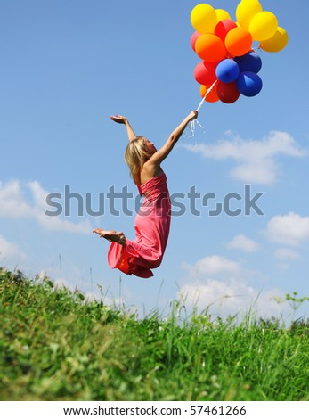 Girl jumping with balloons trying to fly - stock photo