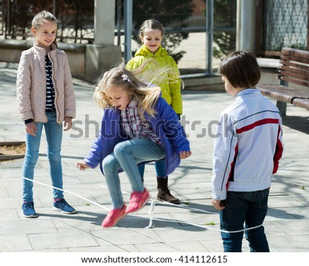 Girl jumping with skipping rope among friends outdoor - stock photo
