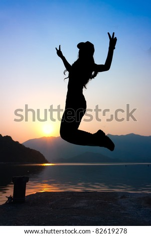 girl jumping with V sign on seaside at beautiful sunset - stock photo