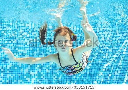 Girl jumps, dives and swims in pool underwater, happy active child has fun under water, kid sport on family vacation  - stock photo