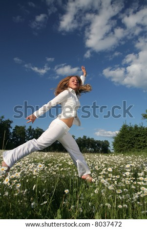 Girl jumps over daisy field in nice summer day
