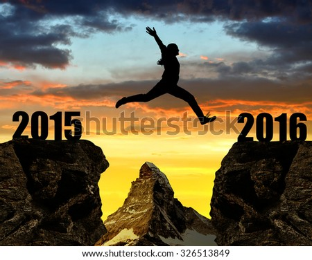 Girl jumps to the New Year 2016 at sunset. In the background Matterhorn - Pennine Alps, Switzerland. - stock photo