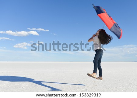 Girl jumps with an umbrella with a vast white salt flats background in Bonneville, Utah - stock photo