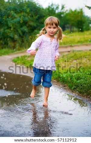 Girl junps barefoot in a puddle splashing water in the rain - stock photo