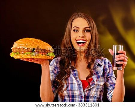 Girl keeps big hamburger and drink. Fastfood concept. Cheeseburger on foreground. - stock photo