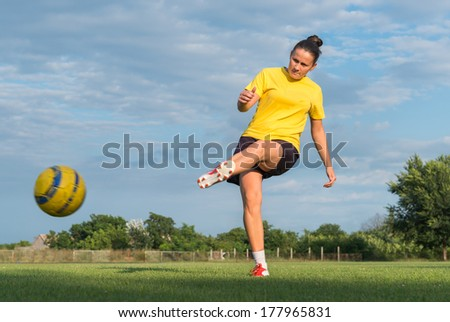 Girl kick soccer ball in field - stock photo
