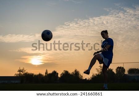 girl kicking soccer ball - stock photo