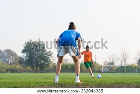 Girl kicking soccer ball toward goal - stock photo