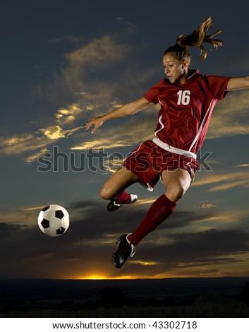 Girl Kicks soccer ball in mid air - stock photo