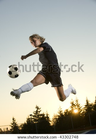 Girl Kicks soccer ball in mid air in the early morning - stock photo