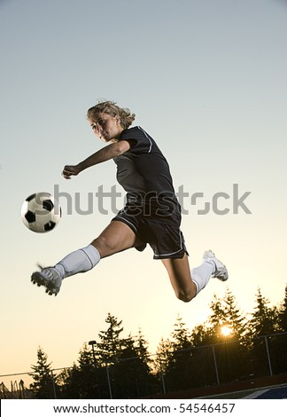 Girl kicks soccer ball in mid air in the early morning. Vertical shot. - stock photo