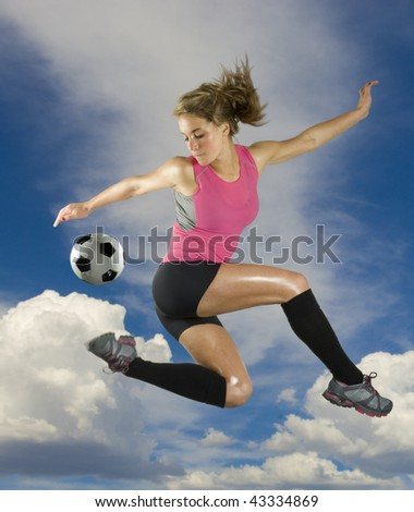 Girl Kicks soccer ball in mid air with clouds in background - stock photo