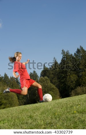 Girl Kicks soccer ball on a field - stock photo