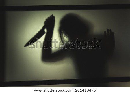 Girl killer with a knife in her hand. Shadowy figure behind glass  - stock photo