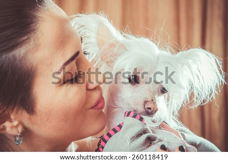 Girl kissing dog breed Chinese Crested