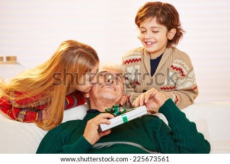 Girl kissing grandfather with gift on the cheek at christmas