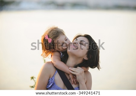 girl kissing her mother in cheek - stock photo