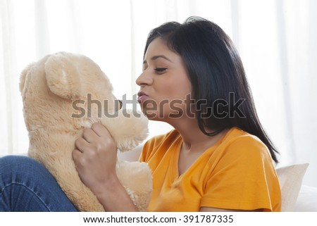 Girl kissing teddy bear