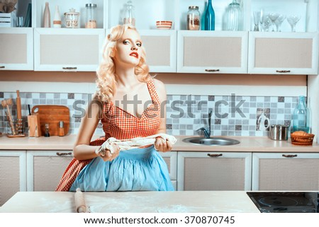 Girl kneads the dough and flirting. She's in the kitchen near the stove cooking dinner. - stock photo