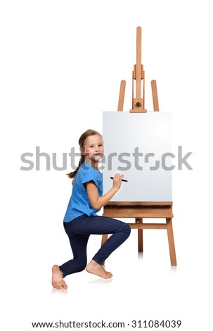 girl kneels and drawing on easel - stock photo