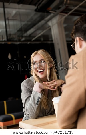 Girl laughing while sitting at cafe with young man