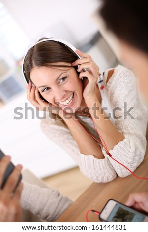 Girl laughing with friends as listening to music