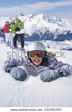 Girl laying in snow with family of skiers standing near on mountain top - stock photo