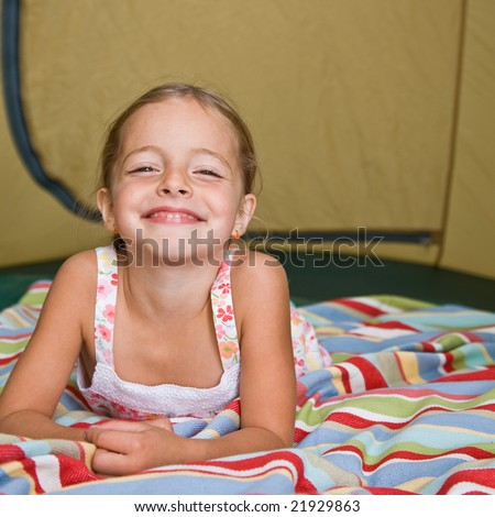 Girl laying in tent - stock photo