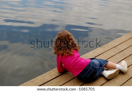 girl laying on a dock - stock photo