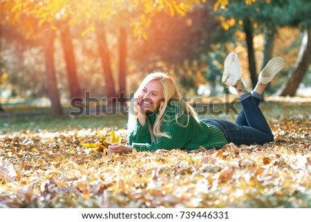 Girl laying on autumn leafs - Stock image