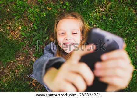 Girl laying on grass with mobile phone. Young teenager girl taking selfie using mobile phone. Cell in girls hand. Using social network. - stock photo