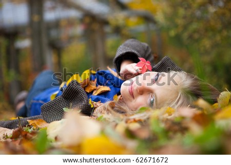 Girl laying on leafs in the autumn park - stock photo
