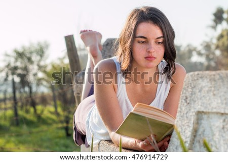 Girl laying on wall reading outdoors