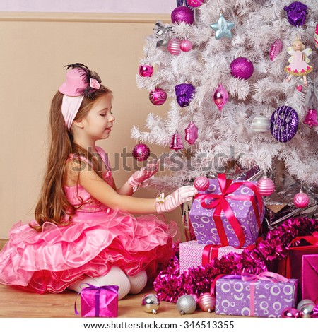 Girl lays out the gifts under the Christmas tree. New Year. Holiday and fun. Merry Christmas. 2017 - stock photo