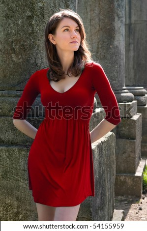 Girl leaning against an ancient pillar - stock photo