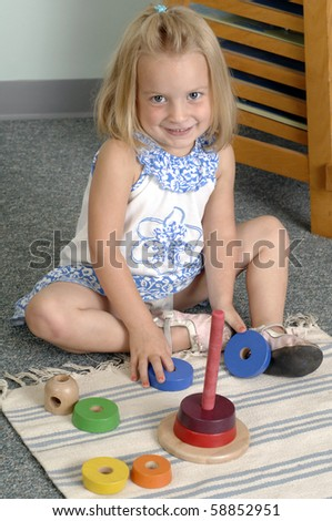 Girl learn while playing with different shapes  at the preschool class. - stock photo