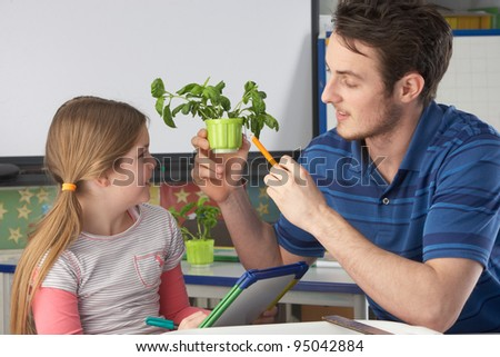 Girl learning about plants with teacher - stock photo
