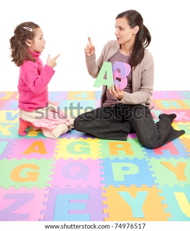 Girl learning phonics alphabet and actions from teacher. Isolated on white - stock photo