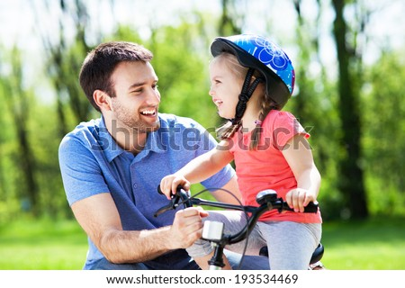 Girl learning to ride a bicycle with father - stock photo