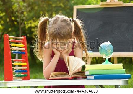 Girl learns lessons in nature. she is reading an interesting book