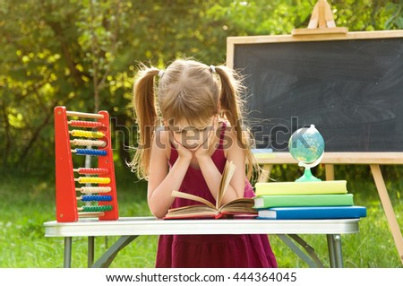 Girl learns lessons in nature. she is reading an interesting book - stock photo