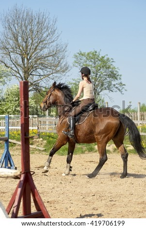 girl learns to ride a horse - stock photo