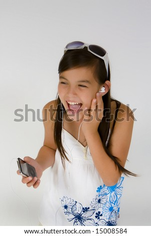 Girl leasining to MP player with headphones on and singing - stock photo