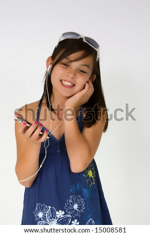 Girl leasning to MP player with headphones on - stock photo