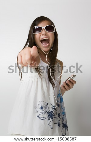 Girl leasning to MP player with headphones on and singing - stock photo