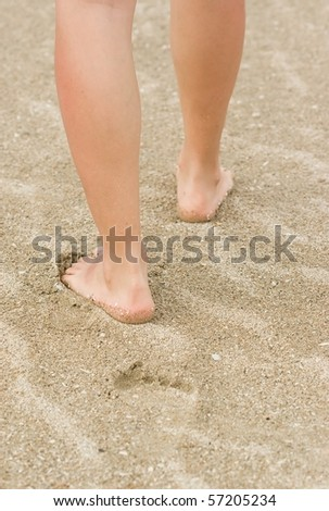 Girl legs in sand near sea,vacation abstract.