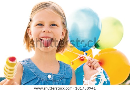 Girl licking ice cream and holding a balloons